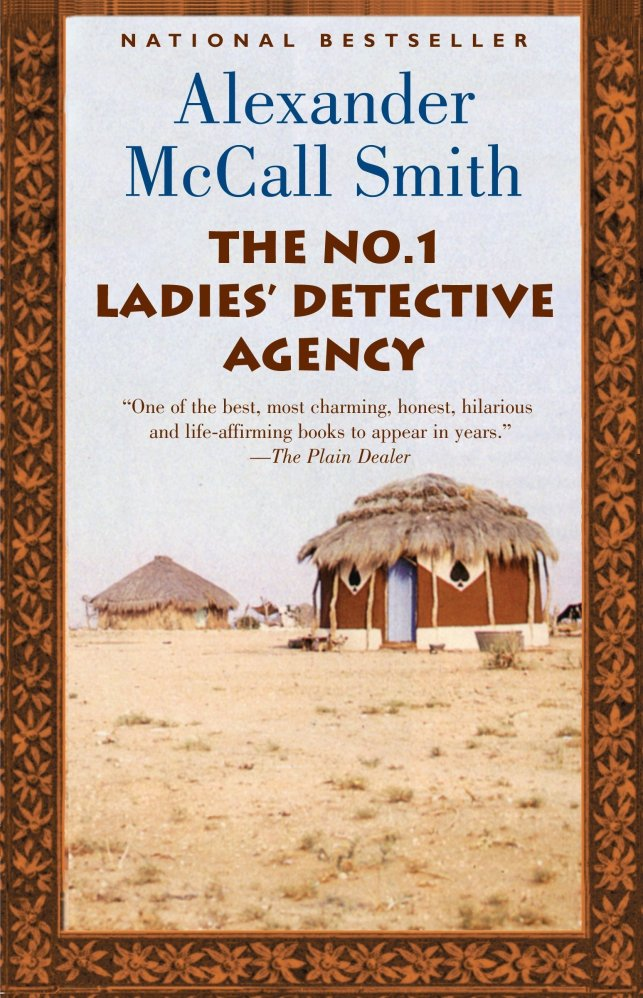 The author and title of book appear above the image of traditional African homes, with thatched roofs. Photograph surrounded by golden and black floral border.
