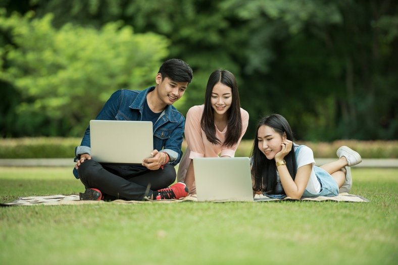 The photograph shows three students, two girls and a boy, looking at their laptops while sitting on a blanket outdoors.