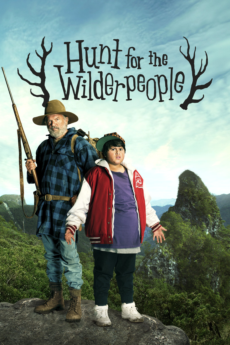 "At the top, it reads ""From Taika Waititi director of What We Do in the Shadows."" Across an almost clear blue sky is the title ""Hunt for the Wilderpeople"" flanked by antlers.  Three figures are shown in close up profile - one is an adolescent boy wearing a cheetah print trucker hat, the next is a bearded man wearing a hunting hat, and the last one is a boar that appears to be mid-laugh.  Across the bottom, there are grasslands and forested mountains shrouded in mist."
