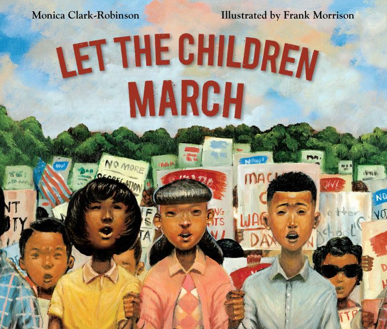 With blue sky and green trees in the background, a set of three Black children are seen in front of a crowd of protest signs. One girl is wearing a yellow polo shirt, one girl is wearing a pink argyle sweater set, and the boy is wearing a blue button down shirt.