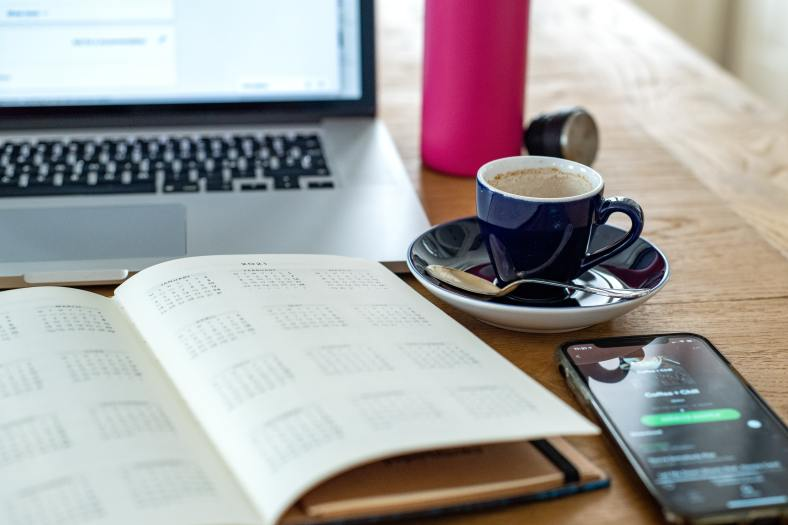 The picture shows an empty coffee cup and spoon, a cell phone, and an open notebook-style calendar in front of a laptop on a wooden table.