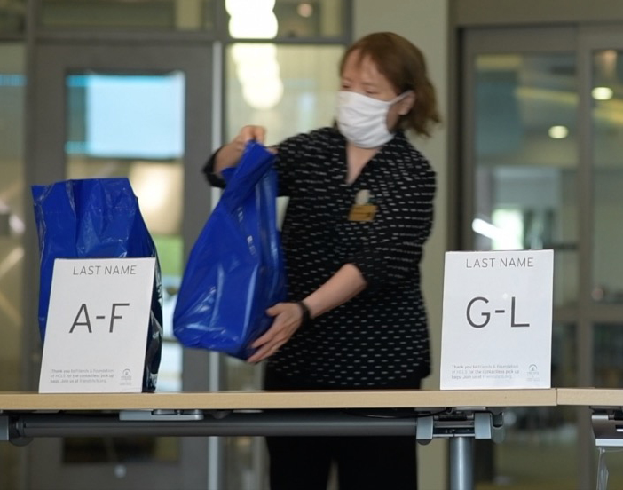 A library staff member, wearing a face covering, places blue bags on a table with alphabetic signs, A-F and G-L.