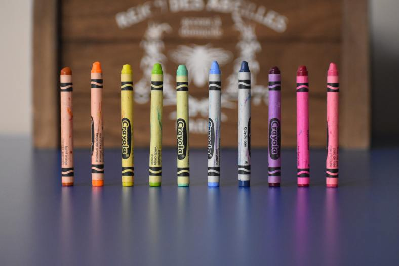 A row of crayons in rainbow colors stands on end, with a blurred wooden crate in the background.