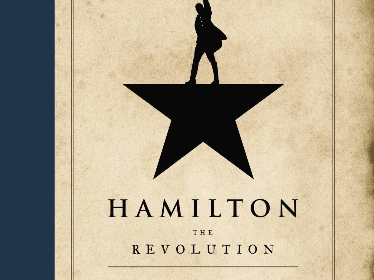"4/5 of a black star against a parchment background, with Hamilton standing on the ""platform"" with his arm raised. Text reads, ""Hamilton the Revolution."""