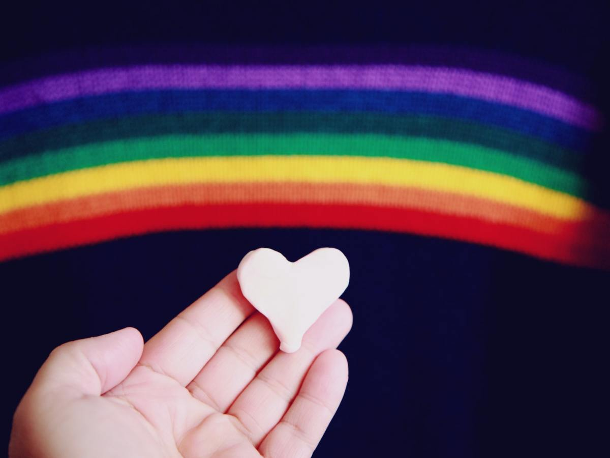 The photograph shows an open hand holding a white ceramic heart, with a rainbow above on a dark background.