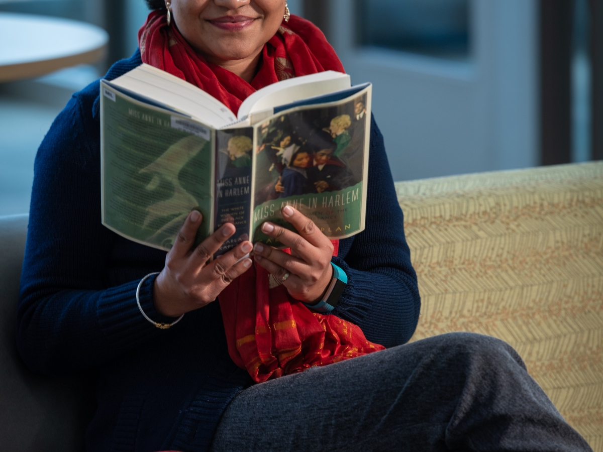 Library employee sits on a sofa with an open book in her hands, smiling at the camera. Other books are piles around her.