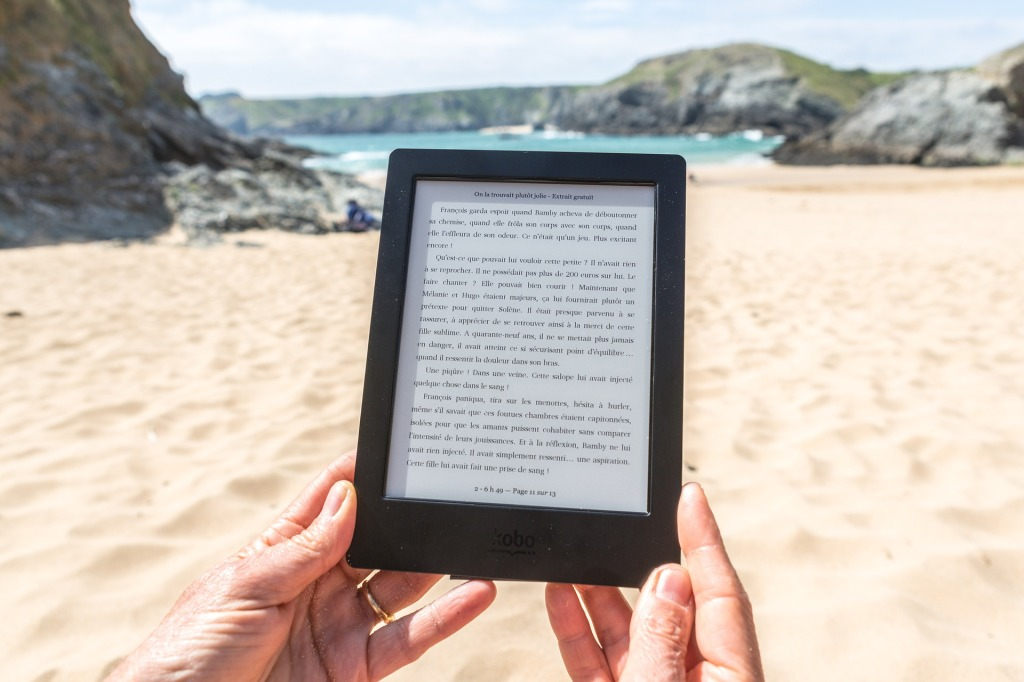 The image shows a pair of hands holding an ereader with a remote sandy beach, rocky hills, and a turquoise sea and hazy blue sky in the background.