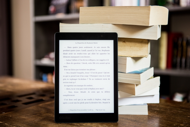 The image depicts an ereader on a wooden table, leaning up against a stack of nine paperback books, with a bookcase in the background.