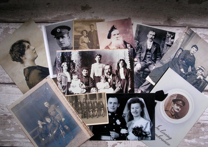 Collage of old photos including military and wedding portraits fanned along wooden table.