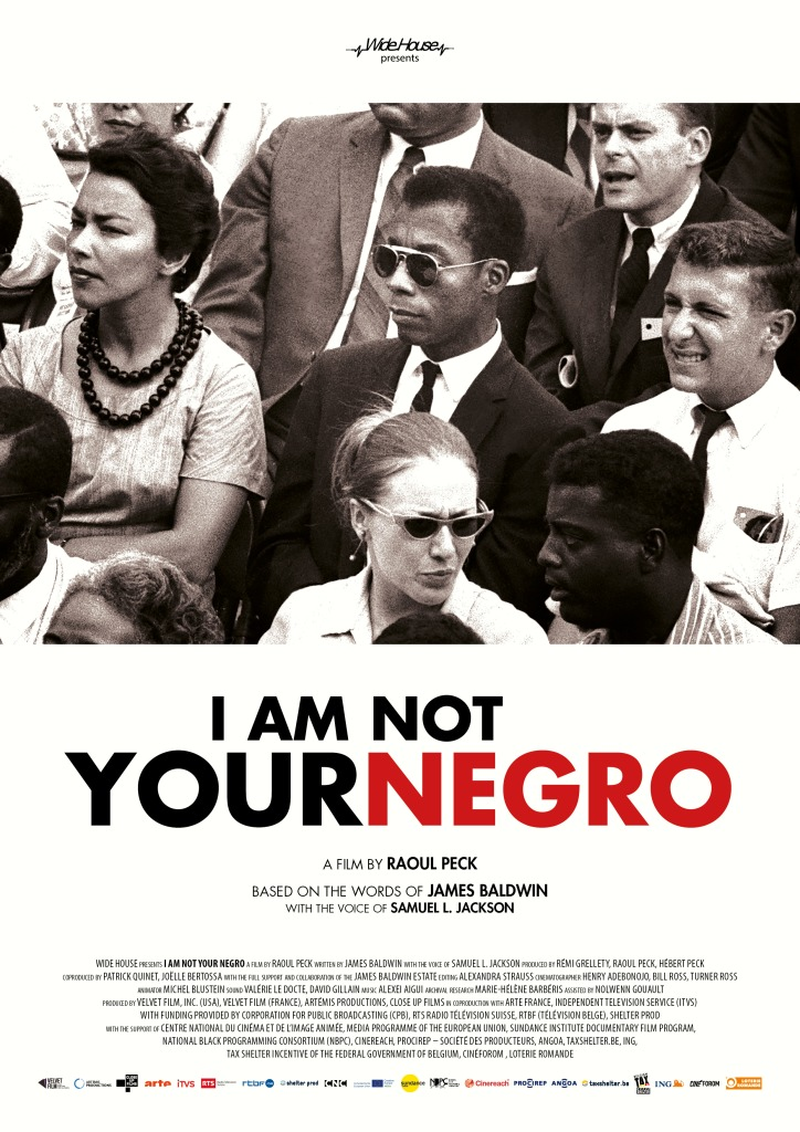 Black and white photo from the 1950s or 60s with James Baldwin in the center, wearing a suit and sunglasses. Title appears below photo withe the word Negro in read.