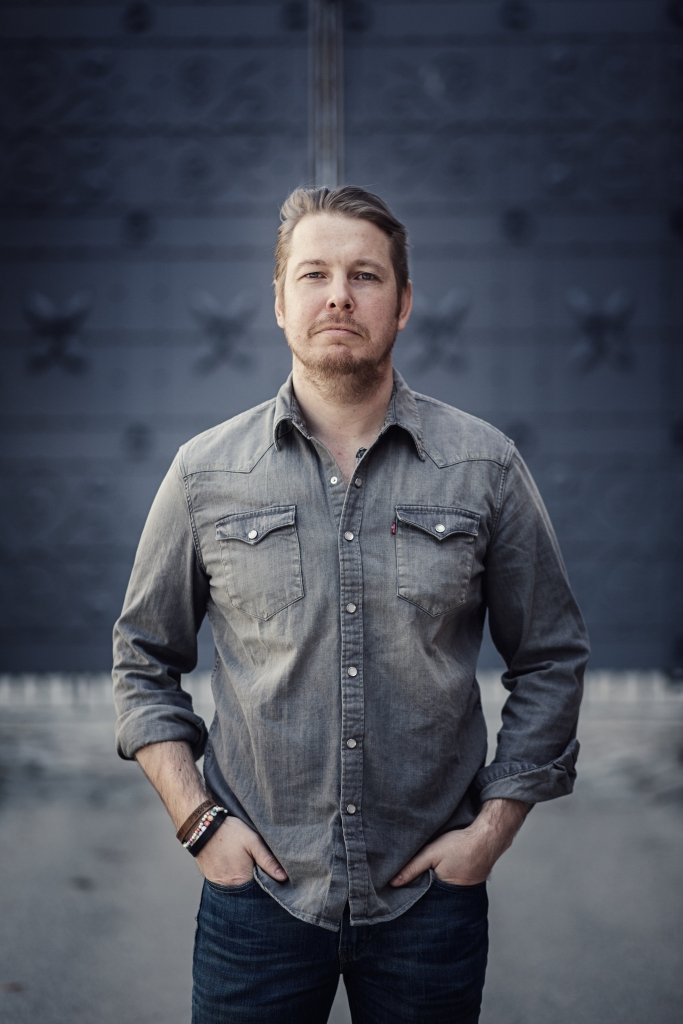 The author, dressed in a dark grey button down shirt, stands with his hands in his jeans pockets. He has short brown hair, and a slight beard.