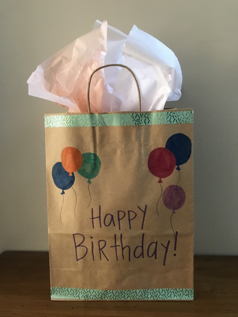 Brown paper bag decorated with marker and tape to say Happy Birthday, with tissue paper sticking out from the top.