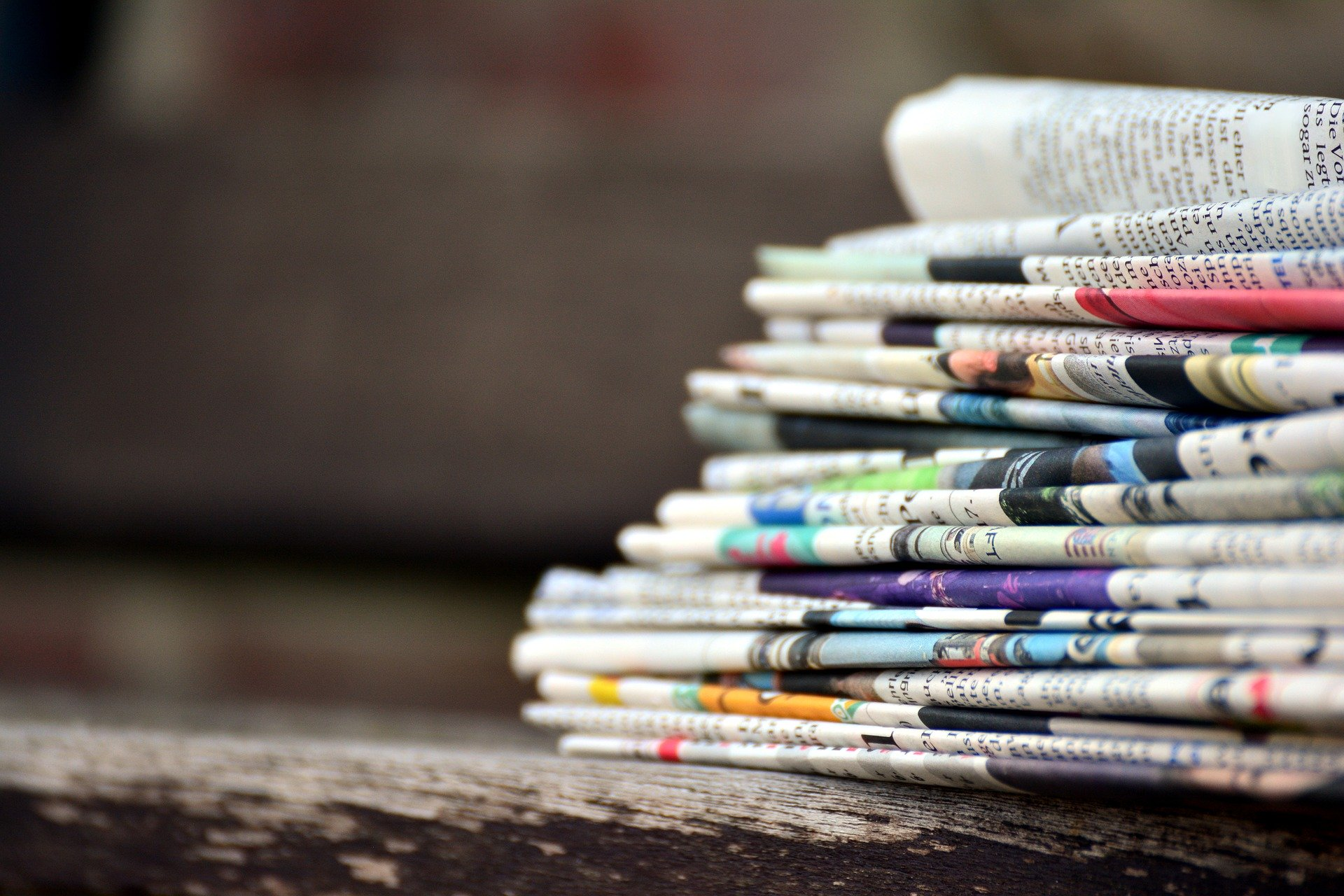 Stack of folded newspapers sits in right hand
