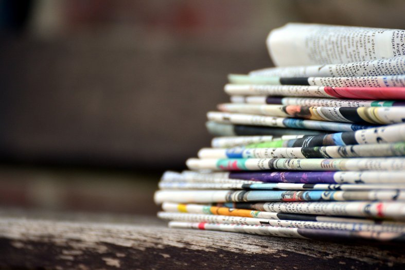 Stack of folded newspapers sits in right hand part of photo, with background blurred.