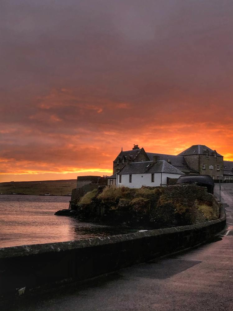 The picture depicts the sun setting behind a promontory on the island of Lerwick in Shetland, with several old buildings and a walled road approaching them.