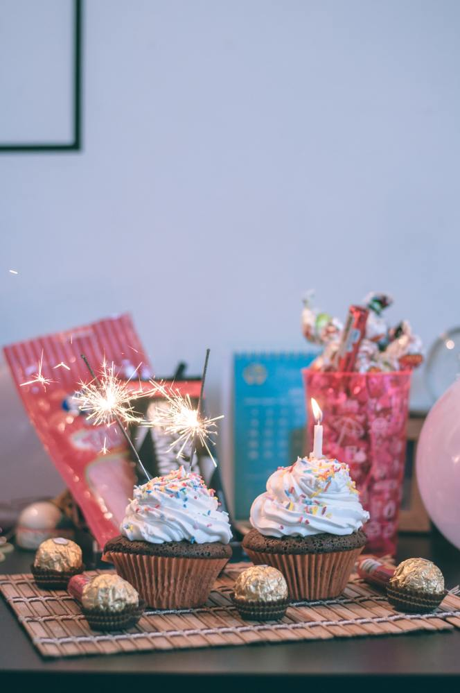 Two cupcakes with white icing and multicolored sprinkles are in the foreground. One has a candle and one has two sparklers. They are surrounded by wrapped chocolates and sitting on a placemat. In the background are party favors, balloons, and gifts.