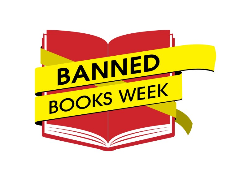 "The image depicts a red book on a white background, wrapped in yellow tape with the words ""Banned Books Week"" written on it in black."