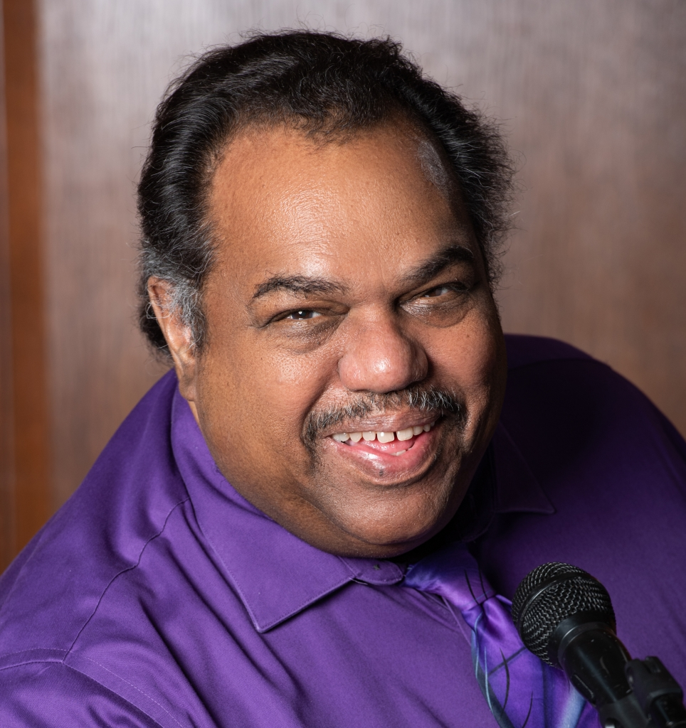 Smiling image of Daryl Davis, Black man with greying temples and mustache, wearing a purple shirt and tie and sitting in front of a microphone.