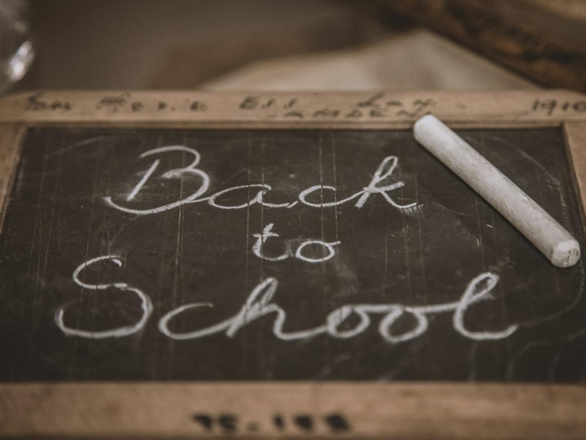 """The picture shows a handheld chalkboard with """"Back to School"""" written on it in cursive with white chalk. The chalk is resting on the chalkboard."""