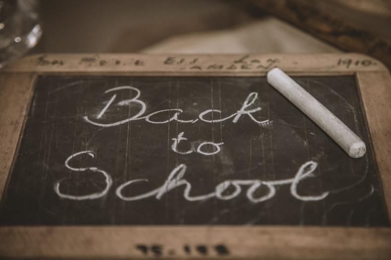 "The picture shows a handheld chalkboard with ""Back to School"" written on it in cursive with white chalk. The chalk is resting on the chalkboard."