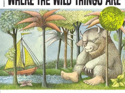 """The cover depicts one of the """"wild things"""" of the title sitting at the water's edge among a forest of trees, with an orange sailboat with yellow sails headed in its direction."""