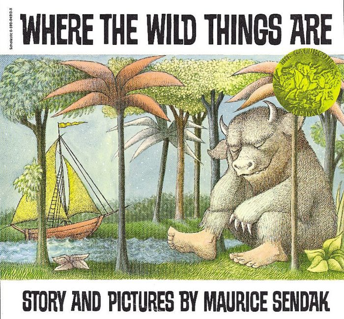 "The cover depicts one of the ""wild things"" of the title sitting at the water's edge among a forest of trees, with an orange sailboat with yellow sails headed in its direction."