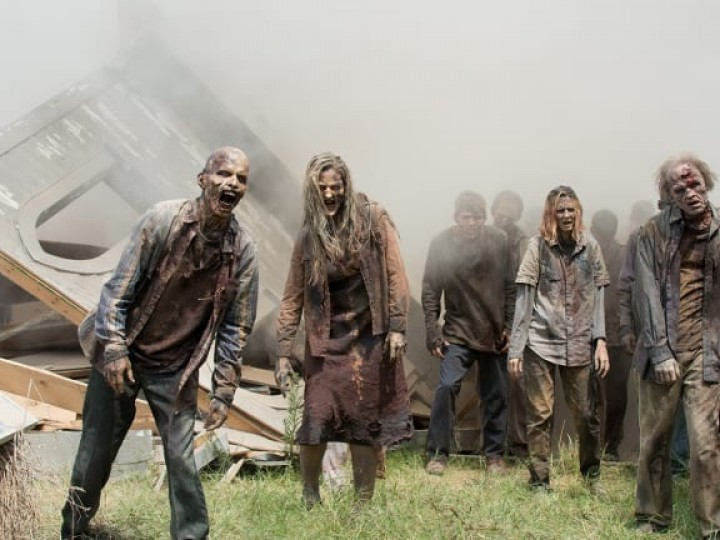 A crowd of zombies stagger past the wreck of a building, coming out of dense fog.