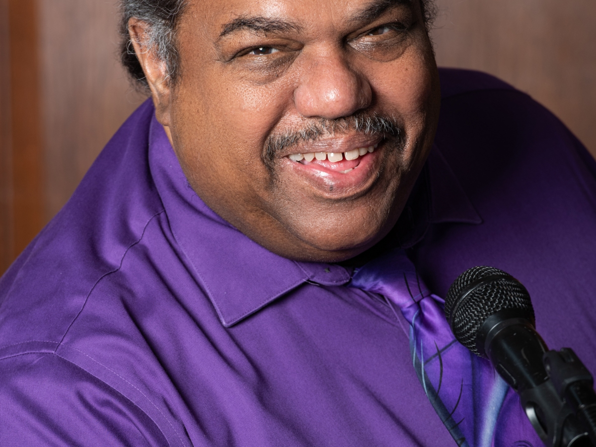 Headshot of a smiling Daryl Davis, wearing a purple shirt and tie, seated in front of a microphone.