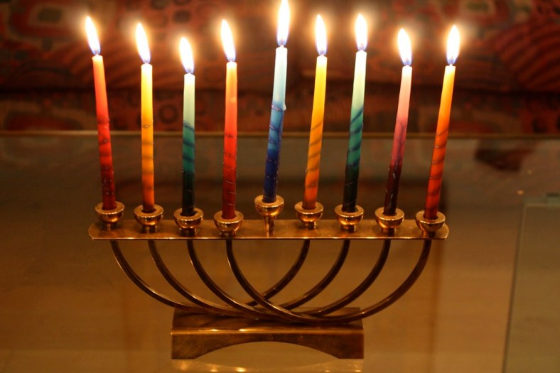The photograph depicts a tabletop menorah with nine lit candles in primary colors.