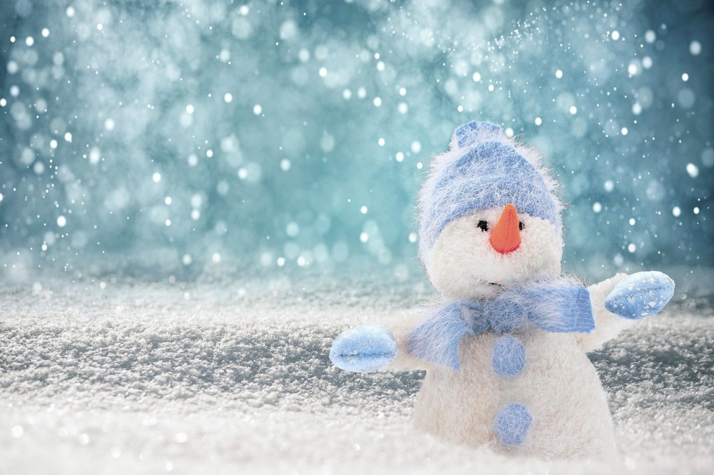Snowy background with a white felt snowman wearing light blue scarf, mittens,. and hat.