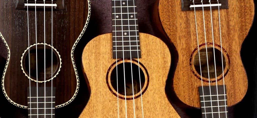Three ukuleles, set alternating top to bottom, in three finishes - dark, blond, and maple.