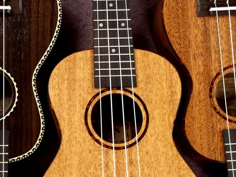 Three ukuleles, set alternating top to bottom, in three finishes - dark, blond, and maple.