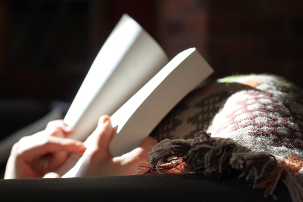 The photograph depicts two hands holding an open book against a colorful woolen blanket, with sunlight streaming in to illuminate the book.