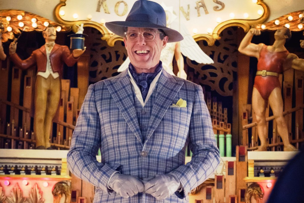 Hugh Grant is depicted in a blue and grey checked suit with ascot, and a blue wide-brimmed fedora, in front of a carnival-themed calliope.