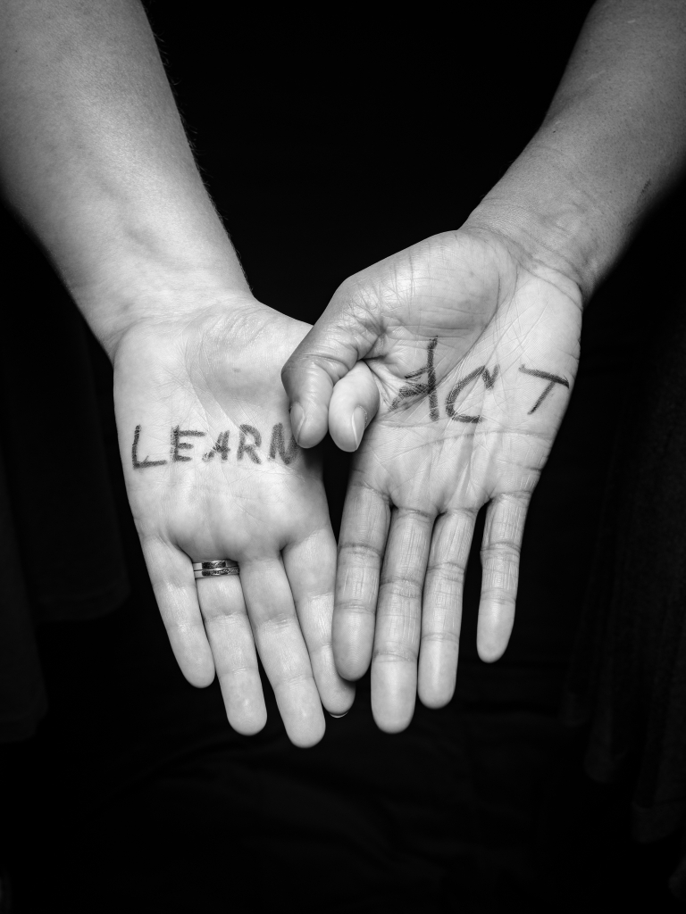 "Two hands joined by hooking thumbs. The hand on the left is White and has the word ""Learn"" on the palm. The hand on the right is Black and says ""Act."""