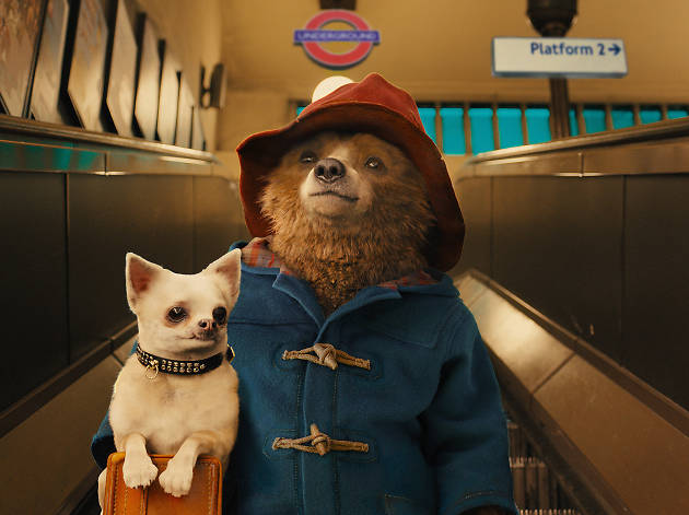 Paddington is shown in his blue coat and red hat, riding an escalator with a small white dog with a jeweled collar.