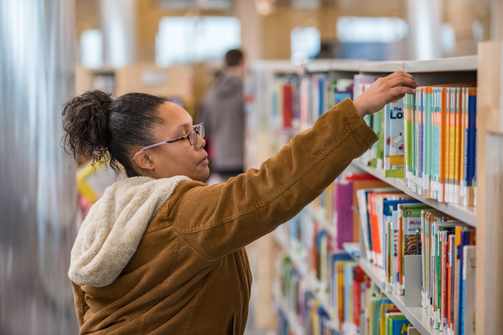 A woman, with a ponytail and glasses and wearing a light brown corduroy coat, reaches for a book off a library shelf.