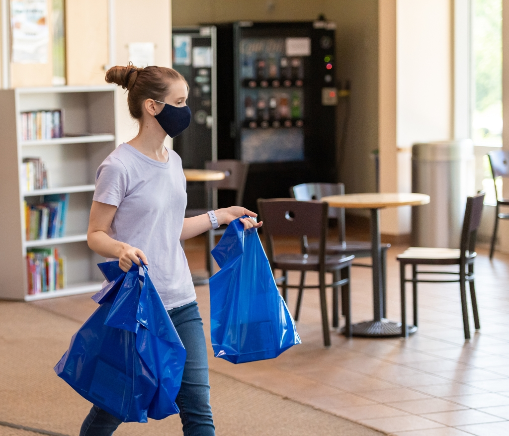 A Glenwood Branch staff member walks across the cafe carrying contactless pickup bags.