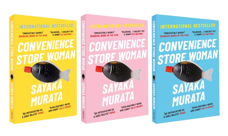 Three copies of the book, in yellow, pink, and pastel blue, each feature a plastic fish containing a dark liquid and a red stopper at its mouth.