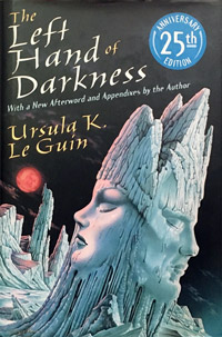 "The cover of ""The Left Hand of Darkness"" depicts a lunar-like surface with two opposite-facing profiles carved out of rock, against a dark sky."