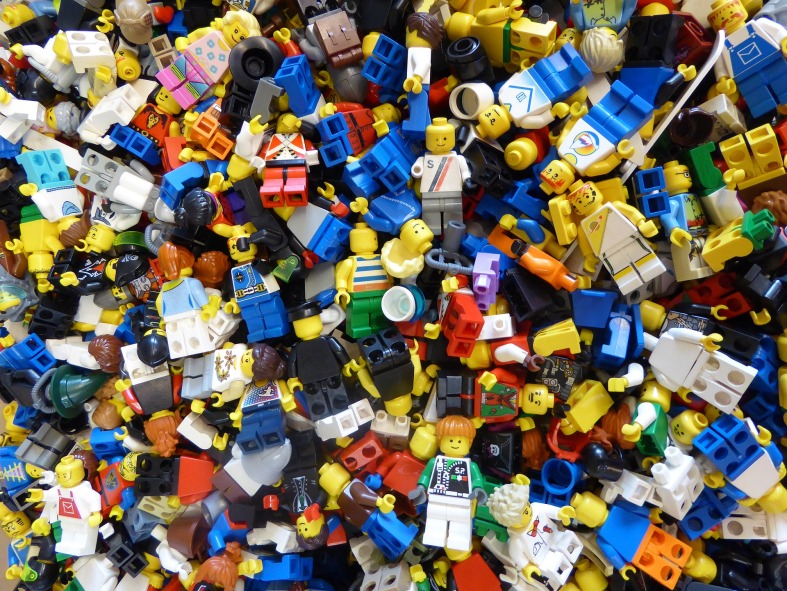 The photograph depicts a jumbled, colorful pile of Lego blocks and figurines.