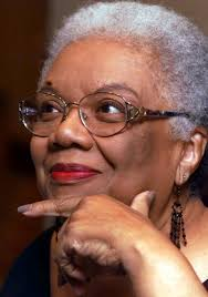 The photograph is of poet Lucille Clifton, looking to her right and smiling with her hand on her chin.