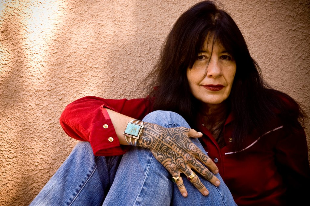 The photograph depicts poet laureate Joy Harjo wearing a bright red shirt and blue jeans, with her tattooed hand across her knee and a turquoise bracelet on her wrist.
