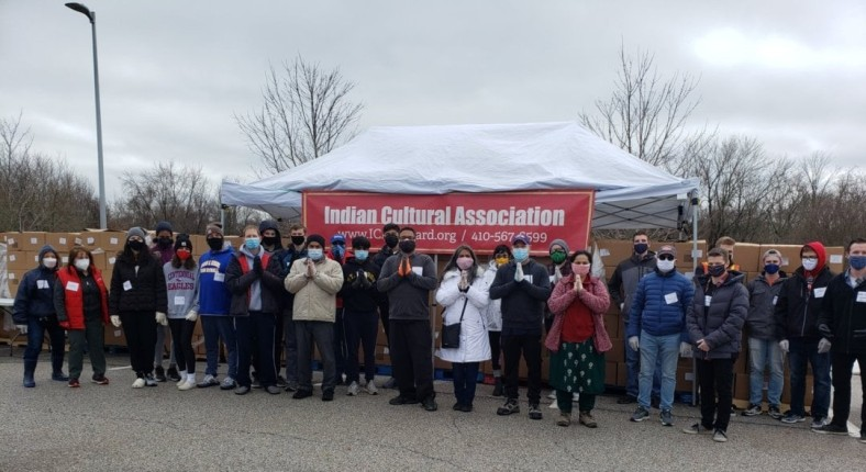 A group of people in winter coats and masks stand in front of a white pop-up tent, from which hangs a red banner that read Indian Cultural Association.