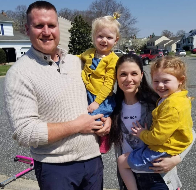 A family of four stands together outside, with parents holding children wearing bright yellow shirts.