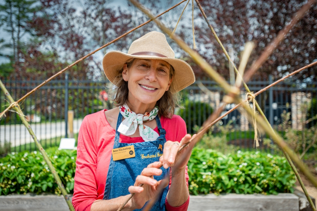 Photo of Enchanted Garden Coordinator Ann Hackeling with a trellis. She's wearing a bright pink shirt, a floral scarf, a blue apron, and a straw hat while smiling at the camera.