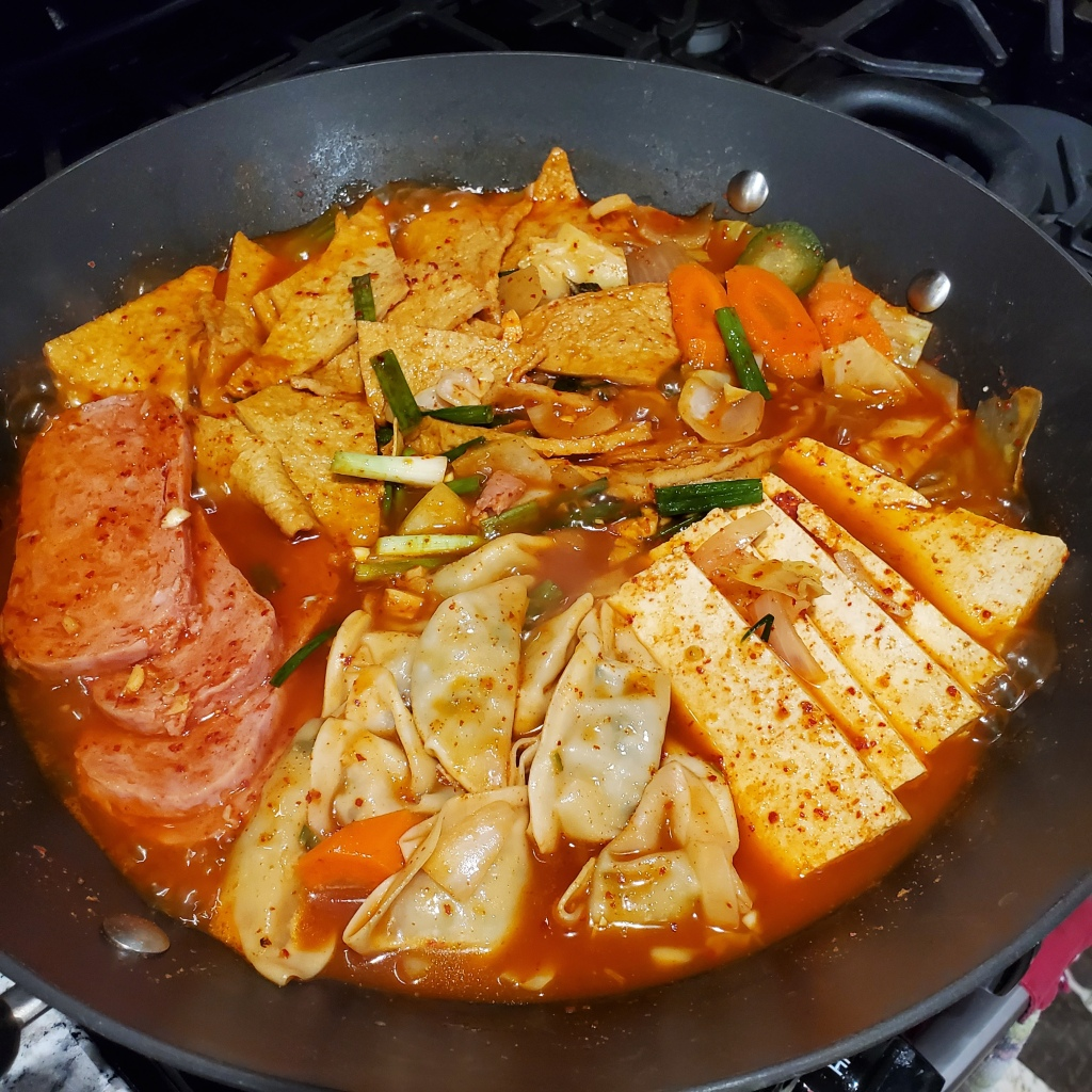 The photograph of budae jjiajae shows a pan of kimchi-based stew with spam, vegetarian dumplings, tofu, and fish cakes in a spicy red pepper sauce.