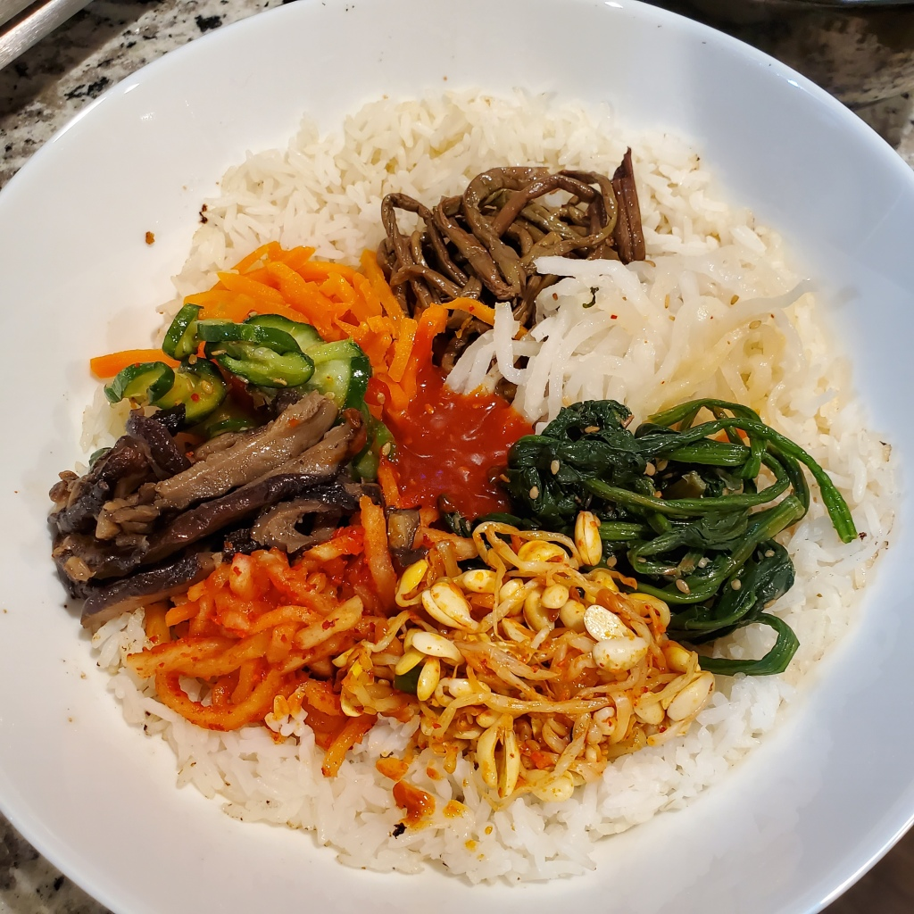 The photograph is of bibimbap on a white plate containing bean sprouts, spinach, pickled carrots, cucumbers, pickled radish, mushrooms, and red pepper sauce on a bed of white rice.