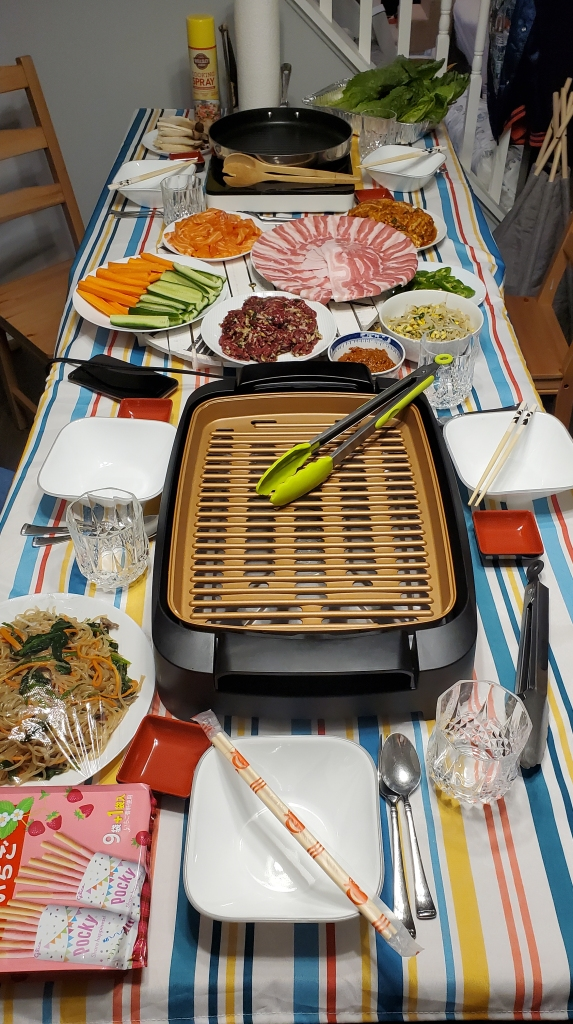 The photograph of place settings and table service shows plates, glasses, a smokeless grill with tongs, chopsticks, and a variety of meats and vegetables for grilling, all against a bright tablecloth in summer colors.