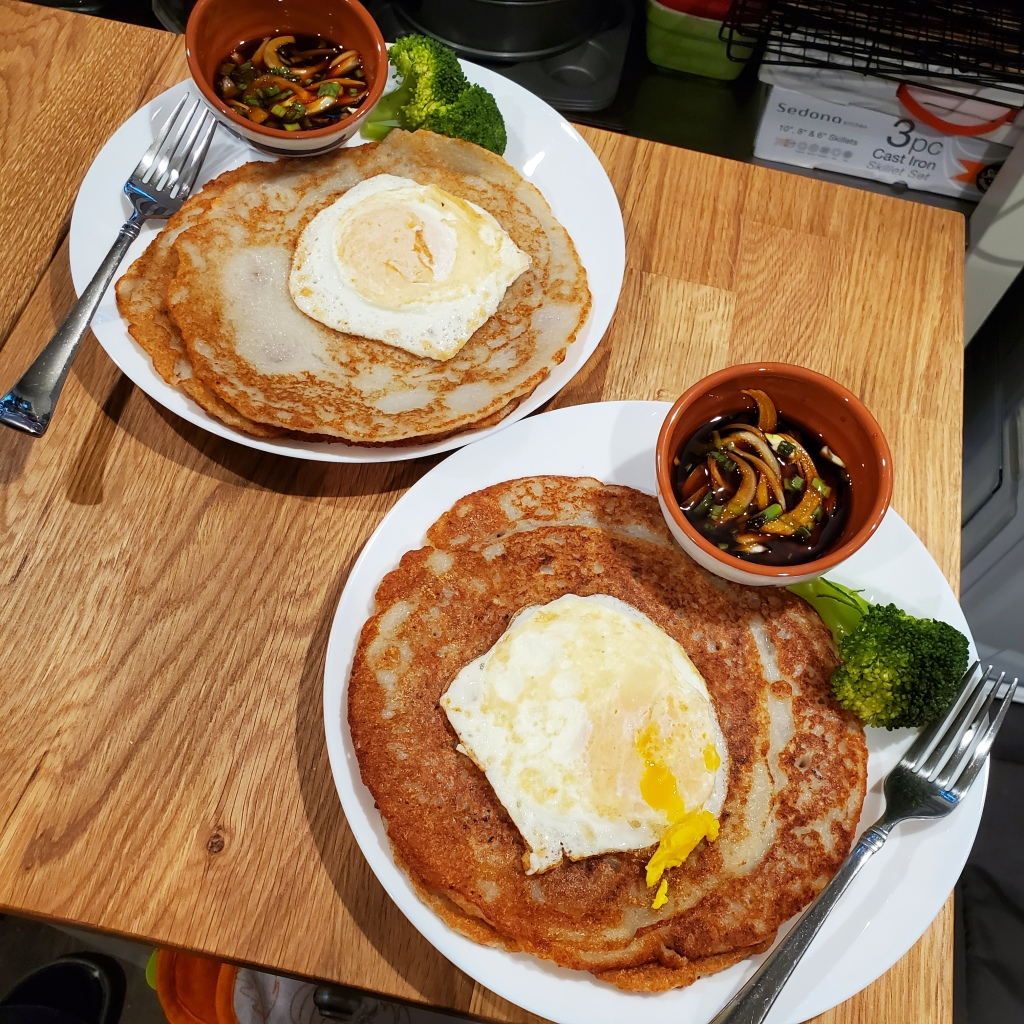 The photograph of potato pancakes shows pancakes on two white plates with forks, with a fried egg on top and served with a bowl of soy dipping sauce with onions and peppers and a broccoli garnish.